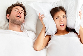 Frustrated woman covering ears next to snoring man