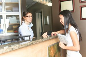 person talking to dental receptionist