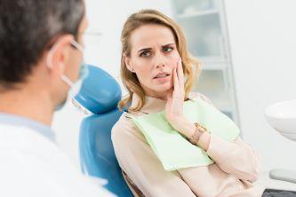 Woman in dental chair touching her cheek
