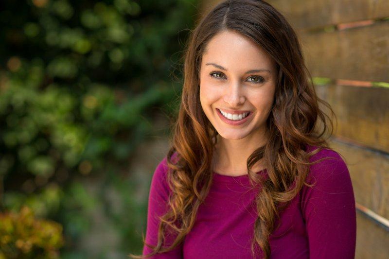 A woman smiling outside.