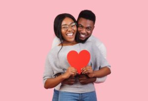 young couple in gray sweaters holding red heart