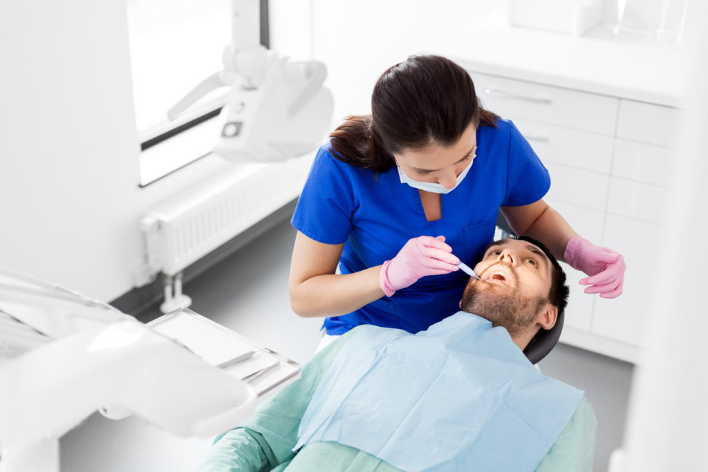 A dentist examines a patient's mouth for signs of disease.