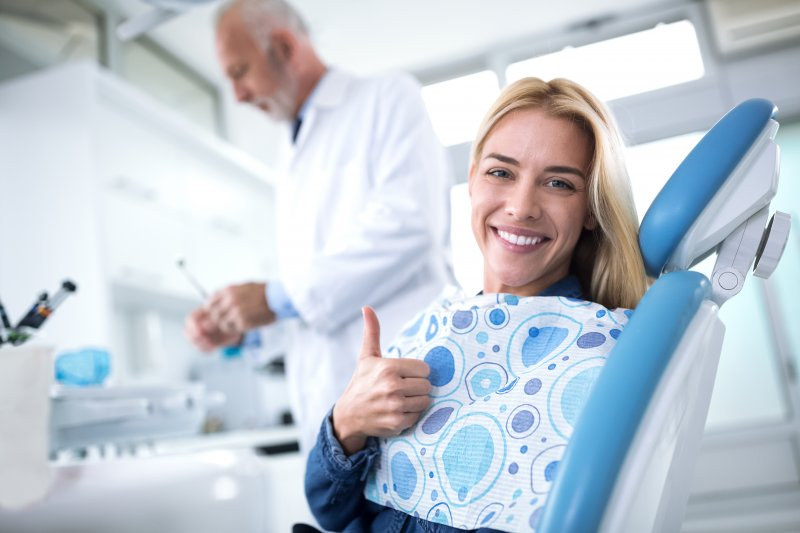 Woman giving thumbs up at dental visit