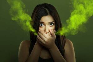 Woman covering her mouth with her hands and green odors coming from her hands