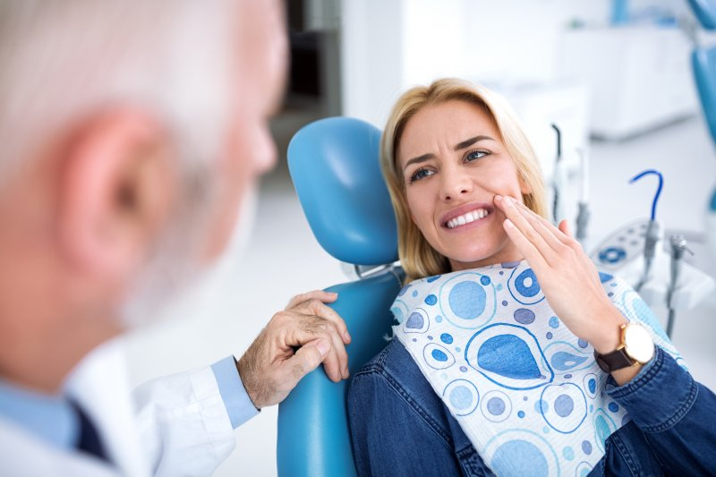 Woman talking to dentist about tooth pain