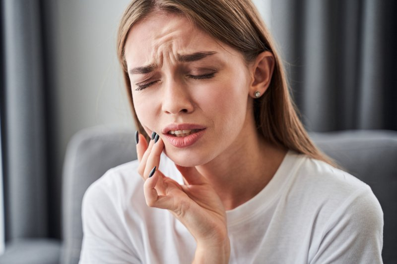 girl in pain touching her cheek with fingers
